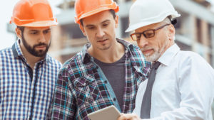 three men in hard hats discuss covid safety meaures on tablet